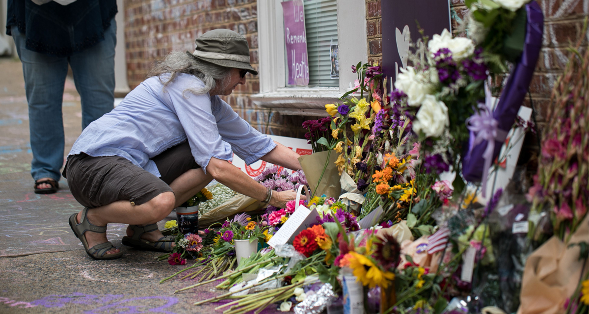A woman places flowers on a makeshift memorial dedicated to Heather Heyer off the mall in downtown Charlottesville, Virginia, one-year after the violent white nationalist rally where Heyer was killed and dozens of others were injured.