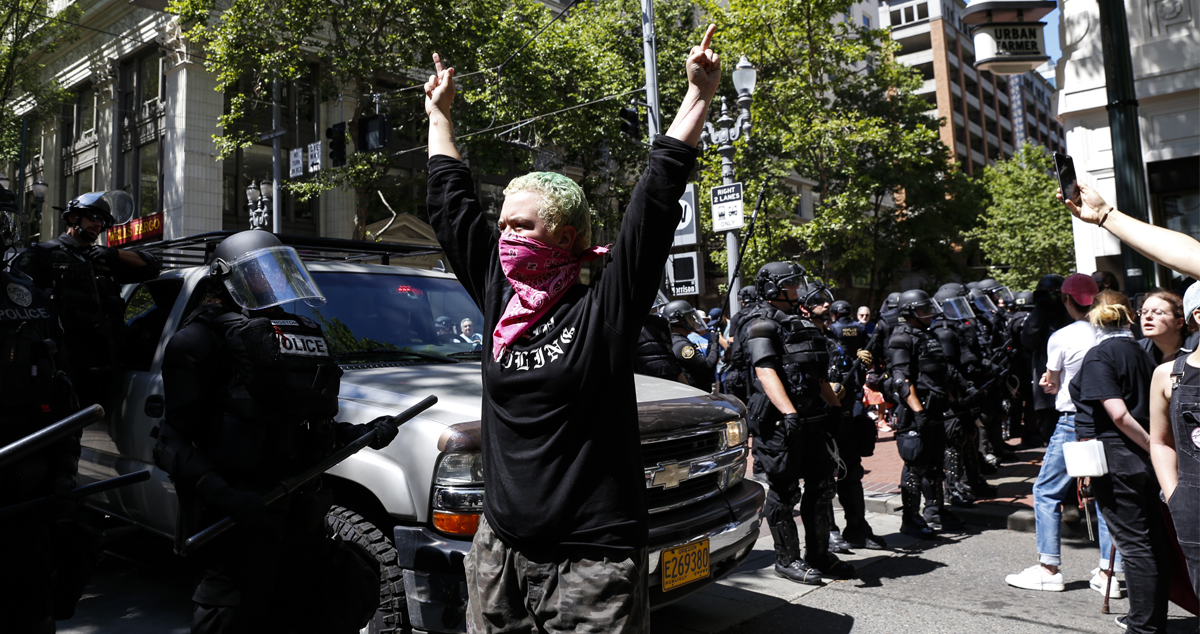 An unidentified Rose City Antifa member flicks off to the police during a demonstration between the left and right at Pioneer Courthouse Square on June 29, 2019 in Portland, Oregon.