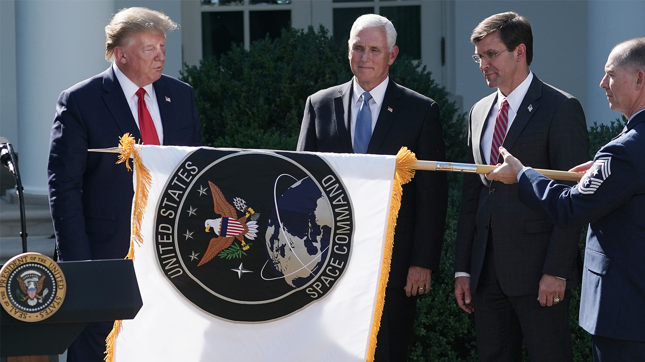 U.S. President Donald Trump, Vice President Mike Pence and Defense Secretary Mark Esper watch as the flag for the new the U.S. Space Command is revealed in the Rose Garden at the White House August 29, 2019 in Washington, DC.