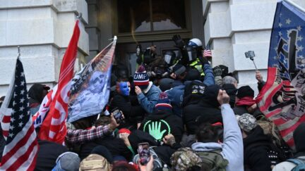 Dozens of pro-Trump supporters storm an entrance to the US Capitol