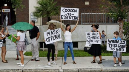 TAMPA, FL - JULY 27: Families protest any potential mask mandates before the Hillsborough County Schools Board meeting held at the district office on July 27, 2021 in Tampa, Florida. The Centers for Disease Control and Prevention recommended those who are vaccinated should wear masks indoors including students returning to school. (Photo by Octavio Jones/Getty Images)
