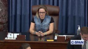 Kyrsten Sinema wearing a demin vest in the Senate chamber